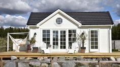 """Attefallshuset """"Heidi"""" är ett ljust och rymligt bygglovsfritt hus på 25 kvadratmeter med yttermåttet 7,15 x 3,50 meter.Detta hus har både ett rymligt allrum med ett fullutrustad kök, hall med gott om förvaring. Badrummet är tillgänglighetsanpassad. Loftet som har en nockhöjd på 107 cm kan användas som både sovloft och förvaring. Huset har en totalhöjd … New England Hus, New England Cottage, Small Cottage Plans, Bungalow Extensions, Summer Cabins, Porch And Balcony, Little Cottages, Tiny House Cabin, White Cottage"""