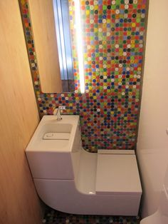 Sink filtered and used to flush toilet in this efficient bathroom.  The wall is covered with plaques made with recycled bottle caps.