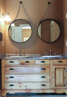 Antique dresser re-purposed as master bathroom vanity. Metal-rimmed mirrors hung by heavy rope completes the rustic look.