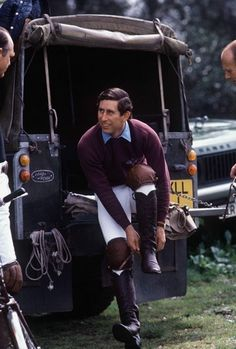 Prince Charles gearing up at the back of a Land Rover.