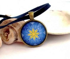 Blue & Yellow Mandala pendant. Handmade and set in an antique bronze bezel setting. BLUE represents emotional healing, inner peace and meditation; Yellow is learning, wisdom, laughter and happiness. @jewelsforhope @oneartsymomma @blownawaymarket @Inthewildkitchn