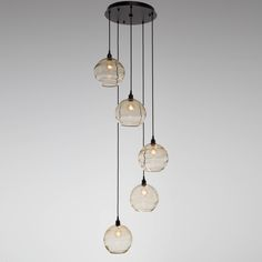 This 'Terra' globe shade, on this multi-port chandelier, achieves its stunning effect from a molten glass ribbon that is wrapped by hand around the glass bubble during production. Shown here: Terra Round 5-Piece Waterfall, CHB0047-05, in Matte Black finish and Amber Optic Blown Glass