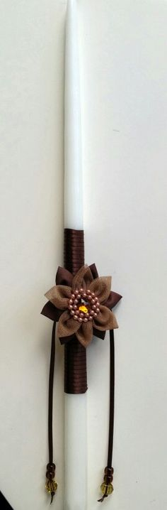 """18"""" easter candle lambada.  Perfect for an older girl.  Brown flower with ribbon.  Simple and elegant design.   $ 20.  Contact us at maro@oneiromou.com Easter Candle, Candle Sconces, Wall Lights, Ribbon, Candles, Elegant, Brown, Simple, Flowers"""