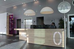 """Sinds medio 2013 is het hoofdkantoor van Pluryn gevestigd in Nijmegen. Het 4 verdiepingen tellende bedrijfspand is aan de binnen- en buitenzijde volledig gerenoveerd en geschikt gemaakt voor """"het nieuwe werken"""". Het ontwerp is van Eric van Beuningen van Croonen architecten. Hubbers interieurmakers heeft het beeldbepalende vaste meubilair mogen maken, waaronder de ontvangstbalie."""