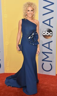 KIMBERLY SCHLAPMAN in a one-shoulder Gauri & Nainika gown with a large rosette at the waist, plus a matching Tyler Ellis clutch and statement Lydia Courteille earrings.