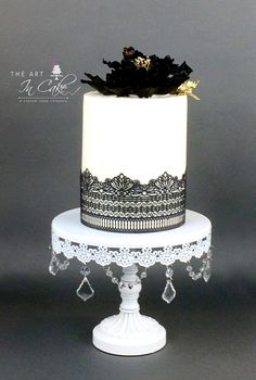 Tall buttercream cake wrapped in black cake lace and topped with a sugar peony and gold accents.