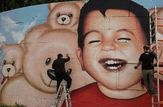 Graffiti artists Oguz Sen, left, and Justus Becker put the finishing touches to a new mural of the drowned Syrian refugee Aylan Kurdi, at Osthafen in Frankfurt am Main, Germany on July 4, 2016. After the previous picture was daubed with slogans, the new image shows a living, laughing Aylan surrounded by teddy bears. (Photo by Boris Roessler/DPA via ZUMA Press)