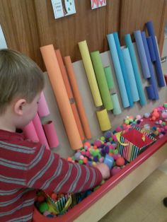 sensory table pom pom made with wrapping paper tubes and painted.  Sent the pom poms with bubblegum sent. Fine motor