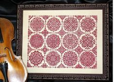 Ink Circles Rosetta - Cross Stitch Pattern. Model stitched on 40 Ct. Espresso Linen with Gloriana Silk floss. Stitch Count: 261 x 197.