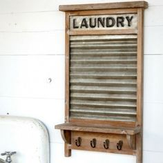 This laundry wash board shelf, featuring a metal washboard and embossed laundry sign surrounded by a distressed wood frame and four hooks, is sure to add a little vintage farmhouse charm to any laundry room. Washboard Decor, Rustic Decor, Farmhouse Decor, Vintage Farmhouse Décor, Old Washboards, Laundry Shelves, Laundry Decor, Home Remodeling Diy, Decoration