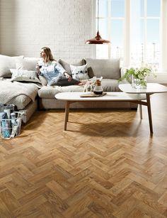 Giving the effect of reclaimed wood flooring which looks great in living rooms like this, Designatex vinyl flooring in English Oak Parquet uses natural timber colours and grain patterns to give an authentic look.