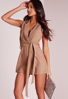 Add a touch of luxe to your wardrobe in this D ring wrap romper. In a totally on trend shade of taupe, this little beaut will be your new go to piece. Featuring D ring detail in a wrap over style, pair with barely there heels and an elegant...
