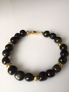 Mens Black Obsidian Pebble Beaded Bracelet with Gold Accent Beads Black Obsidian pebble beads are a large size pebble shaped bead which gives the bracelet interesting curves. Beads measure 7-8 mm. Gol