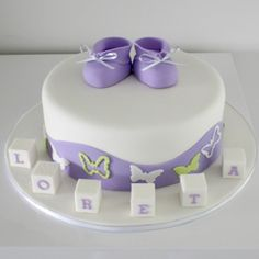 Purple and Lime Butterflies - a modern christening/naming day cake with a gorgeous colour scheme. Icing booties ontop, a wavy side pattern and iced name blocks on the board. www.classiccakes.com.au