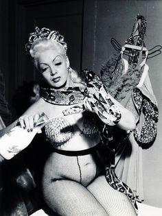 Burlesque dancer Zorita, feeds her pet snake Elmer, New York, 1952. °