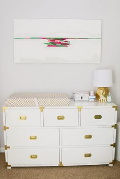 Love the pops of gold in this white campaign dresser/changing table in the nursery - Project Nursery