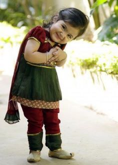Indian baby girl. Her smile and costume is so lovely. She wears a Indian traditional clothes