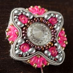 Close up of pink and silver infused Soutache pin brooch. Kits available to buy at Create and Craft - http://www.createandcraft.tv/SearchGridView.aspx?fh_location=//CreateAndCraft/en_GB/$s=soutache&gs=soutache