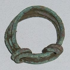 circa 9th - 11th Century AD Anglo Saxon/viking Finger Ring  A twisted wire copper-alloy finger ring possibly dating to the late Anglo-Saxon or the post medieval period. The wire is circular in section, uniform in width and coiled three times to form the band, the ends of which are wrapped around the hoop to bind them together. Made from multiple bands with a bezel of knotted appearance, is more likely to belong to the late Anglo-Saxon period with the arrival of Viking culture.