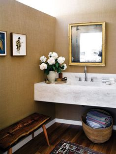 The powder room's rare 19th century mercury mirror with 14-carrot gold leaf paint hovers above a handsome travertine countertop.  Photo: Douglas Friedman