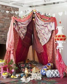 Make a romantic tent for a lovely staycation--saris, quilts, pillows and hanging lanterns.