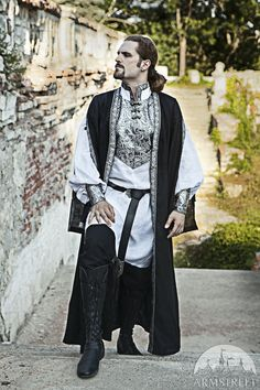 Like the black colour, style and length of this sleeveless coat, not the tunic as its way too elaborate.