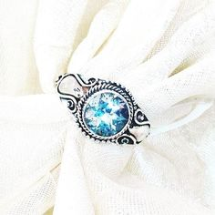 Here we have a nearly 2CT Swiss blue topaz set in Bali-style sterling silver, resizable size 4. A classic. Topaz, the November birthstone, is said to be good for communication, love and attraction, good fortune and good health. It soothes, heals, stimulates, recharges, remotivates