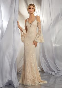 This Boho Inspired Gown Beautifully Combines Romantic Allover Chantilly Lace with a Brilliantly Beaded Neckline and Cold Shoulder Detail. A Scalloped Hemline and Bell Sleeves Complete the Look. Colors Available: Ivory, Nude.