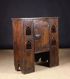A 16th Century Style English Elm Aumbry, made in the 18th century possibly at Wardour Street. The plank top above a single door flanked each side by four Gothic tracery apertures. 44 ins (112 cm) high, 39 ¼ ins (100 cm) wide and 15 ½ ins (39.5 cm) deep.