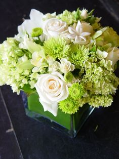 LIKE WHITE hydrangeas, orchids, roses with greenery in glass for centerpieces!