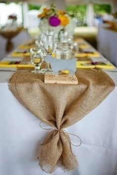 A burlap table runner for a rustic wedding with simple table decorations.