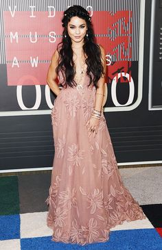 Vanessa Hudgens wears a pink gown with floral embroidery and stacked gold jewelry