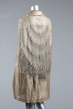 Rare Vionnet embroidered tulle evening cape, circa 1931, labeled and numbered 56783, green on white label with printed thumb-print, the golden tulle ground cut in an arc to the center back, embroidered overall in silver chain stitch with radiating ellipses, edged in gold lame, small button and loop to fasten at the neck with long lame scarf panel.
