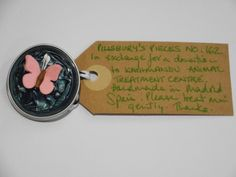 Pillsbury?s Pieces No, 162.  Pin - metallic teal capsule with medium pink paper butterfly.  In exchange for a donation to KATHMANDU ANIMAL TREATMENT CENTRE, Nepal.  Available at St. George's Church, Madrid on Saturday 13 June from 11.00 - 15.00.