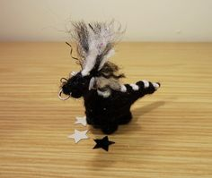 Humbug is a hand knitted miniature dinosaur who gets a little grumpy if he cant find his favourite sweets (humbugs of course!) in the pick n mix stand.  Hand knitted from black acrylic sparkle yarn he loves to make an impression with his hand stitched black and white acrylic yarn spines along his back and his striped mohawk which is made from the same yarns, hand stitched and then brushed to stand on end in a very striking hair do! His look is completed by his tiny nose ring which is made…
