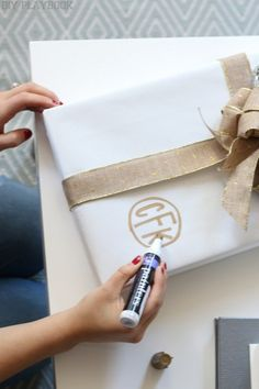 How to make monogrammed gift wrap for Christmas. Add a personal touch to your gifts with a paint marker, and your presents will be that much prettier for the holidays!