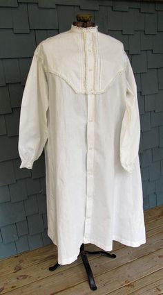 """Mid 19th Century Night Gown: """"The nightgown features a yoked bodice both front and back; the yoke is a double layer of fabric, which adds strength to the shoulders which receive the most wear. There are also reinforcements on the underarms. The front of the yoke and cuffs is trimmed with tucks and white cotton lace. White milk glass buttons the entire front length. Side gussets. All the seams are fully finished, most being flat felled. Measurements: Bust - 50"""", Shoulders - 19"""", Length…"""