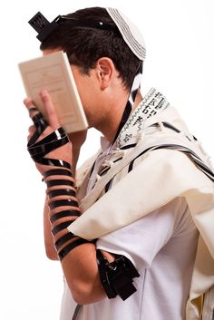 A Jewish teen recites morning prayers wearing tefillin (phylacteries), a set of small black leather boxes containing scrolls ofmore...