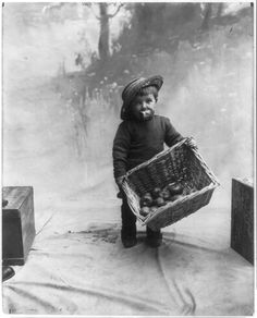 A small boy carries a basket of apples while holding an apple in his mouth in this 1911 photograph. http://www.vanishedamericana.com/kids/proof-of-the-pudding-is-in-the-eating/