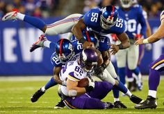 Tight end Kyle Rudolph #82 of the Minnesota Vikings is tackled by cornerback Prince Amukamara #20 and outside linebacker Keith Rivers #55 of...