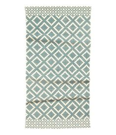 Natural white/gray blue. Rectangular, woven cotton rug with a printed pattern at front.