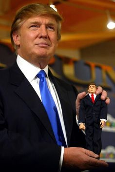 Donald Trump poses with the new Donald Trump 12inch talking doll September 29 2004 at the Toys 'R' Us store in New York City The doll's phrases which...