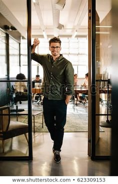 Full length portrait of happy young businessman standing in doorway of office. Caucasian male executive in office with people working in background. Business Portrait, Doorway, Portraits, Leather Jacket, Happy, People, Jackets, Image, Fashion