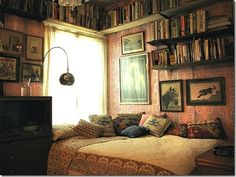 The high book shelf's and the corner bed with lots of pillows and patterns is just so cozy.