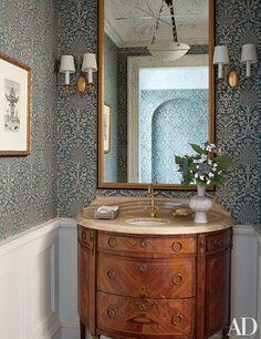 An elegant Long Island powder room designed by Mariette Himes Gomez features a Twigs wallpaper from John Rosselli & Associates.
