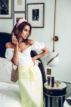 Cute summer date night outfit idea - white off shoulder linen top, silk midi skirt in a soft yellow shade, Cult Gaia bag, and a pink Prada headband #outfit #outfitidea #fashion #style #midiskirt #silkskirt #whitetop #offshouldertop #datenight #headband
