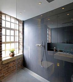 El ladrillo expuesto de la construcción origina crea un interesante contraste con el enchapado gris de gran formato en muros y suelos.