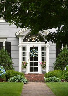 Ein Kranz von gefärbten Hortensien gibt Licht bis vor die Haustür, während ein paar Silber Töpfe mit blühenden Reben geben freundschaftliche Unterstützung zur Dekoration.