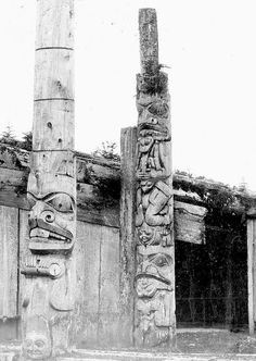 Memorial pole with the beaver holding a stick, and the right corner post. The fully carved corner posts were a feature unique to this house. Directly behind the corner post is a glimpse into the interior. Note the railing around the house pit.