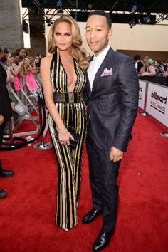 Chrissy Teigen & John Legend, America's current favorite couple, look hot at the 2015 Billboard Music Awards. Surprise surprise! Model Chrissy Teigen looks great in her first outfit of the night, a striped '70s looking jumpsuit by Oivier Rousteing for Balmain with a heavy duty belt.